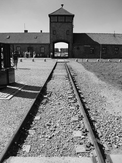 Durch ein hölzernes Tor führen Eisenbahngleise, auf denen Juden in Waggons in das Vernichtungslager transportiert wurden.