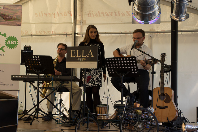 """Auf der Bühne im eigens errichteten Zelt sorgte die Band """"ELLA""""für beschwingte Musik und ein einzigartiges 1:5-Modell des Benz Patent Motorwagens aus dem Bestand des Mercedes-Museums für ein Highlight."""