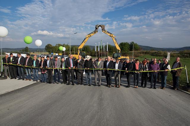 Zwei Bagger symbolisieren den großen bautechnischen Aufwand. Davor durchschneiden zahlreiche Gäste und Beteiligte das Grüne Band und geben so den Weg in den InPark A81 frei.
